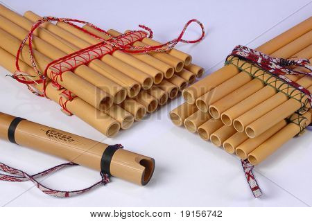 Panpipes and flute on white background