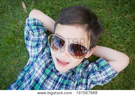 Mixed Race Chinese and Caucasian Young Boy Wearing Sunglasses Relaxing On His Back Outside On The Grass.