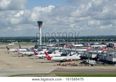 LONDON UK - JUNE 3 2017: View from the air of planes parked at Terminal 3 of London's Heathrow Airport on a sunny summer morning. Virgin Atlantic Delta and American Airlines all use this part of the busy airport.