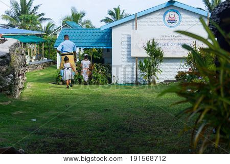 Alofi, Niue - May 29, 2017; Sunday morning a Pacific Island family father in traditional Niue dress leads his two daughters to entrance of Saint Joseph's Catholic Church Alofi Niue
