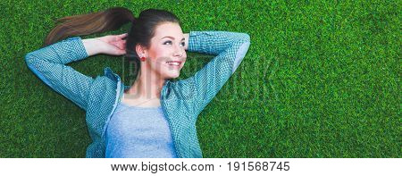 Relaxed woman  lying on the grass with hands on head.