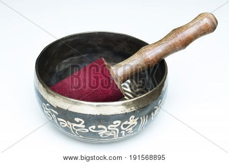 Tibetan buddhist singing bowl with pestle close up. Black metal with golden mantras. White background. Religious object.