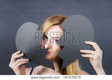 Depression sadness relationship problem concept. Young female with broken heart full of negative sad emotions. Woman covering her face by two parts of black love symbol.