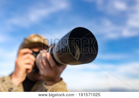 Photographer takes a photo with a large lens .