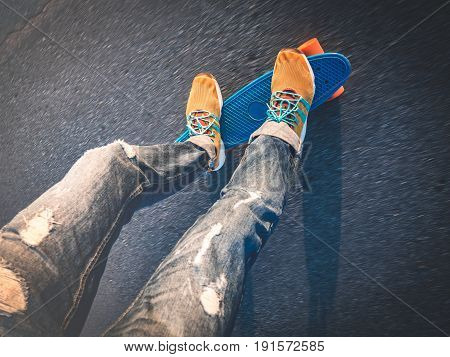 speed: top view of the feet on the skateboard on the pavement