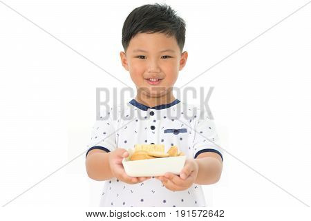 Cute little boy holding cookie isolated on white background