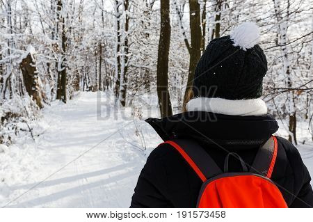 Photo of young woman walking in the forest in wintertime