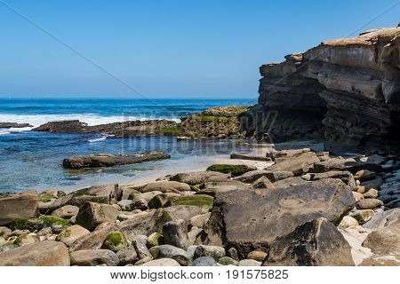 The sandstone cliffs and scattered rocks and boulders at La Jolla Cove in San Diego County.