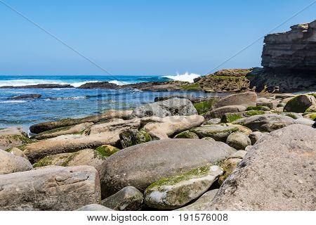 Ocean waves crash onto boulders strewn upon the beach at La Jolla Cove in San Diego, California.