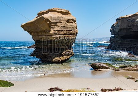 Prominent rock formation with surrounding cliff at the Children's Pool in La Jolla, California.