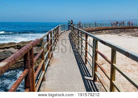 LA JOLLA, CALIFORNIA - JUNE 16, 2017:  Concrete sea wall with railing built in 1931 to protect the sandy beach at the Children's Pool in La Jolla in San Diego County.
