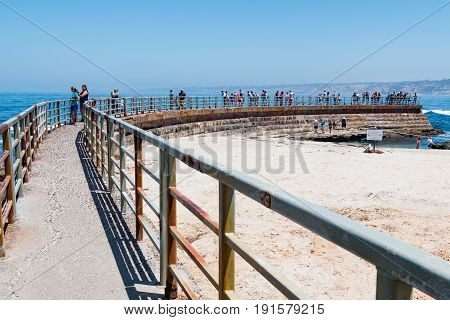 LA JOLLA, CALIFORNIA - JUNE 16, 2017:  Concrete sea wall with metal railing overlooking the Children's Pool in La Jolla, a popular tourist attraction in San Diego County.