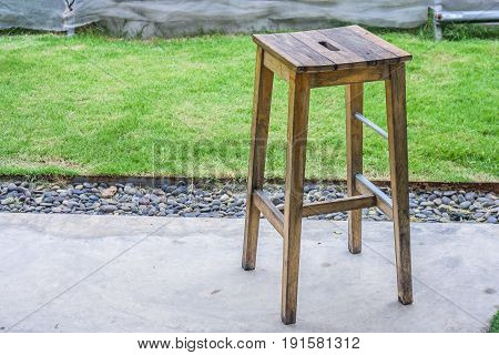 Wooden chair standing on cement floor at outdoor garden.