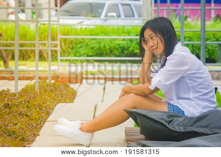 Portrait Asian woman sitting on black pillow and wooden terrace in the garden with green natural background. (Autumn filter effect)
