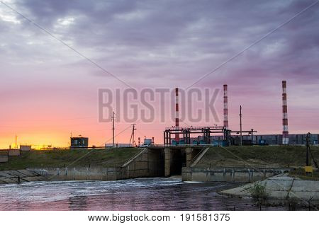 Gas power plant during sunset. Spillway and lake foreground. Energy industry concept.