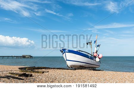 Lonely fishing Boat at the coast and cloudy blue sky.