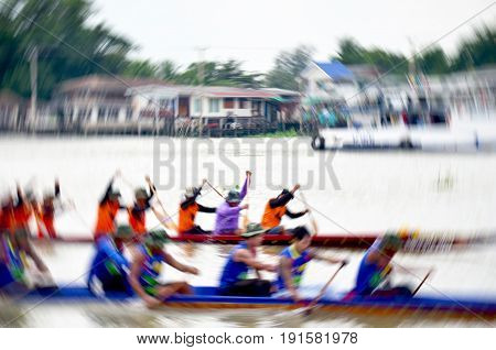 Blurred of motion of Thai people join match and competition in thailand traditional long boat racing festival at Chaopraya river in Nonthaburi Thailand