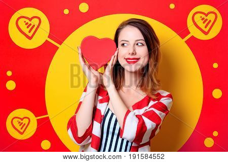 Portrait of beautiful young smiling red-haired white european woman in red striped shirt with heart shape box on yellow background