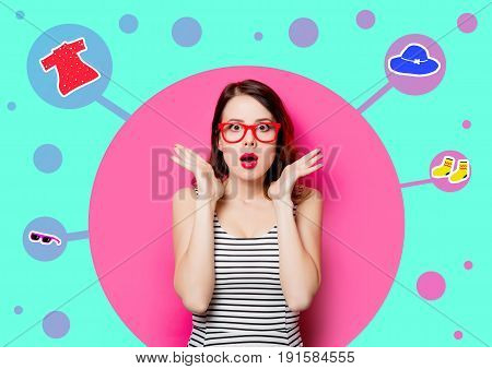 portrait of beautiful surprised young woman in glasses and imagination clothes on the wonderful pink studio background