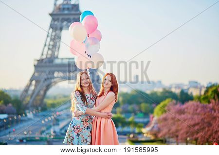 Two Girls With Bunch Of Balloons In Front Of The Eiffel Tower