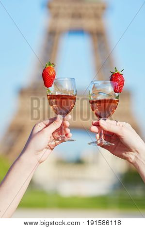 Women Hands Holding Glasses Of Wine With Eiffel Tower In Background