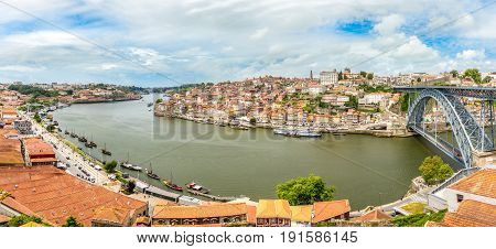 PORTO,PORTUGAL - MAY 13,2017 - Panoramic view at the embankment Ribeira of Douro River with bridge of Luis I. in Porto. Porto is located along the Douro river estuary in Northern Portugal.