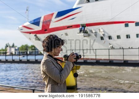 Amsterdam the Netherlands - May 31 2017: woman photographing P&O Aurora cruise ship in Amsterdam