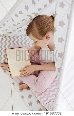 Private nook. Cute bright productive child hiding in a cloth tent in her room for diving into a new story while enjoying her hobby
