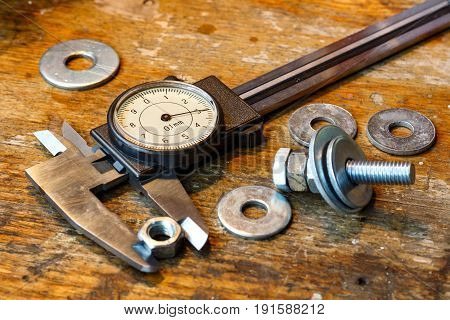 Slide Caliper With Round Scale And Bolt With Nuts On The Workbench In Workshop