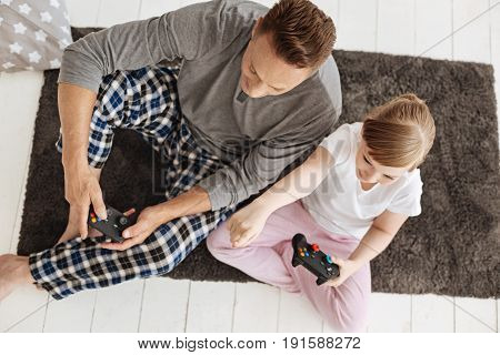 Team work. Imaginative adventurous active family using controllers for playing video games while spending time together and sitting on a rung in a living room