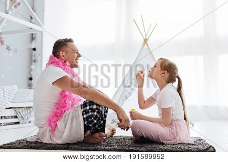 Relaxed mood. Cute imaginative lively child playing with her dad while sitting in her room and entreating him with bubbles