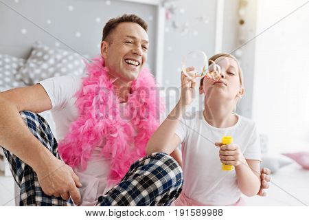 Blow some more. Bright emotional dreamy girl and her parent enjoying their weekend at home and making soap bubbles while feeling happy together