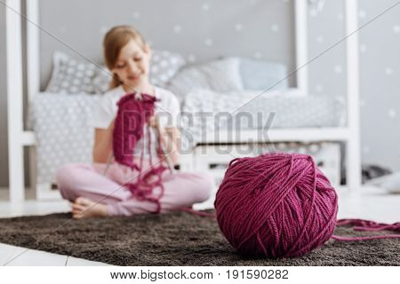 Craft of needles and strings. Gifted attentive focused child spending day at home and learning about new fascinating thing while sitting on the floor in her room