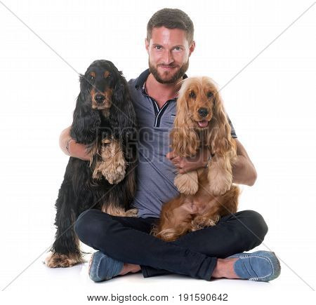 two cocker spaniel and man in front of white background