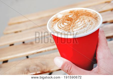 Woman holding a red paper cup with coffee. Coffee to go. Tasty hot beverage on wooden table in sunny day. Outdoors meal.