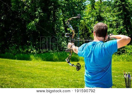 Man in blue shirt shooting his bow an arrow at the range