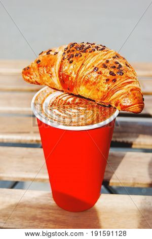 Red paper cup with coffee and chocolate croissant. Coffee to go. Tasty hot beverage on wooden table in sunny day. Outdoors meal.