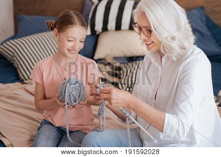 It is easy. Happy positive elderly woman holding knitting needles and showing her granddaughter how to knit while enjoying spending time with her
