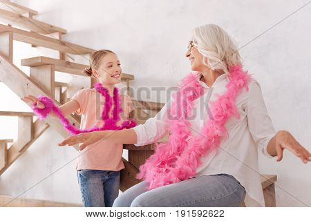 Like ballet dancers. Delighted positive joyful grandmother and granddaughter smiling and having fun together while wearing pink fluffy feather boas