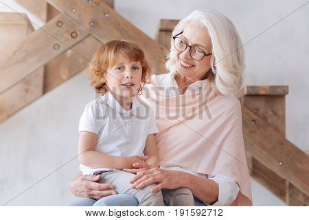 Time for fairytales. Cute pretty nice boy sitting on his grandmothers laps and smiling while being ready to listen to a fairytale