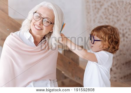 Beautiful hairstyle. Cute pleasant young boy holding feathers and putting them into his grandmothers hair while spending time with her