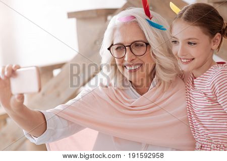 My granddaughter and I. Joyful positive aged woman holding a smartphone and taking a selfie while being with her granddaughter