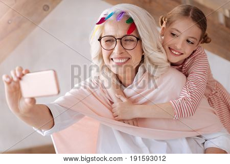 Taking a selfie. Happy delighted positive woman holding a smartphone and looking into the camera while taking a selfie with her granddaughter