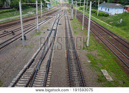 Summer. A cloudy day. Three railway tracks go to the horizon. In the frame sleepers rubble stones poles green trees