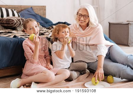 Time together. Happy nice caring grandmother taking an apple and smiling while looking at her grandchildren