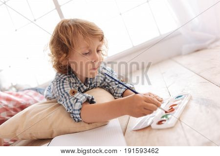 Creating a masterpiece. Nice serious delighted boy lying on the floor and holding a painting brush while creating a masterpiece