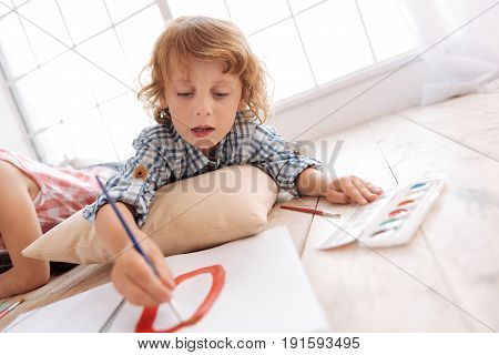 Promising painter. Nice skillful cute boy holding a brush and painting a picture while lying on the floor