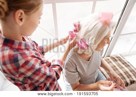 Young hairdresser. Joyful nice skillful girl holding hair rollers and making a hair style for her grandmother while having a great time with her