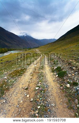 landscape with a rural dirt road and mountain in the background. Altai Russia.