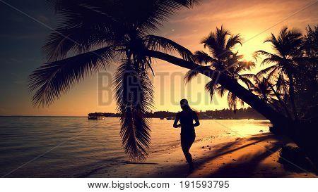 Sea sunrise. Woman running on the tropical island beach Punta Cana Dominican Republic